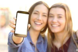 happy friends showing smart phone