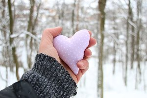 Valentines day card. Hand holding a heart on the background of the winter forest