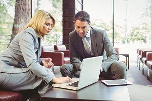 Focused business team having a meeting using laptop