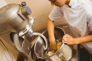 Baker using large mixer to mix dough