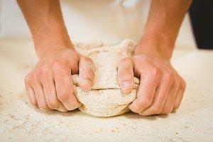 Baker kneading dough at a counter