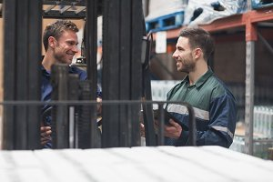 Smiling warehouse workers talking together