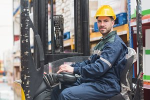 Driver operating forklift machine in warehouse