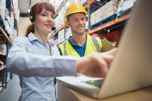 Smiling businesswoman wearing headset using laptop