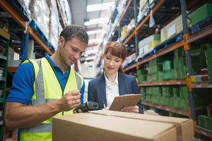 Worker and manager scanning package in warehouse