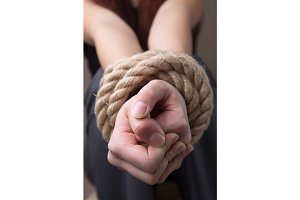 Tied rope hands of girl
