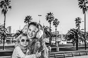mother and child tourists on embankment in Barcelona hugging
