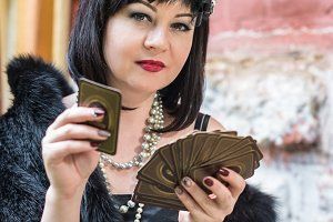 Beautiful retro woman holding playing cards