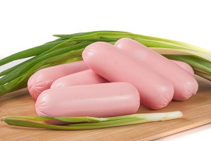 sausages with green onions on a cutting board isolated white background closeup