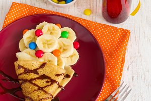 Breakfast for children - pancake with banana, decorated with cho