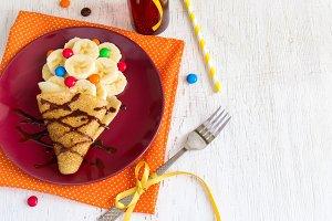 Children's breakfast or dessert - pancake with banana, chocolate