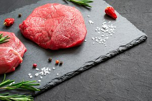 Raw meat beef steaks and rosemary on a black slate board