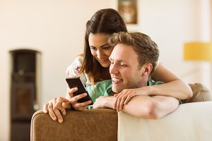 Cute couple looking at smartphone on couch