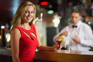 Pretty blonde smiling at camera with cocktail