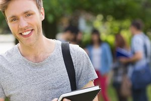 Handsome student smiling at camera outside on campus
