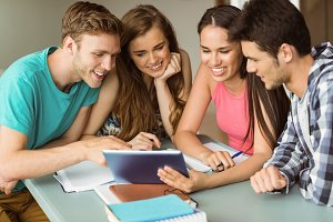 Smiling friends sitting using tablet pc