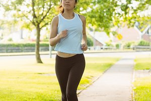 Fit young woman jogging through the park
