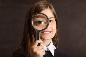 Cute pupil looking through magnifying glass