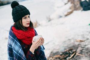 Beautiful girl keeps a large cup of hot tea.