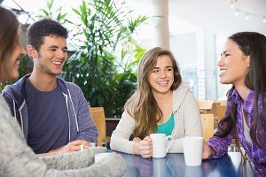 Young students having coffee together
