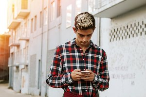 boy with the mobile phone on the city street