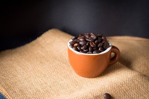 Coffee beans in espresso cup on burlap