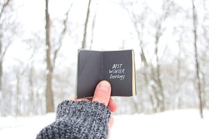Best winter greetings, man holding a book with the inscription