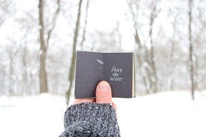 Enjoy the winter, man holding a book with the inscription