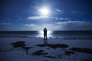 Silhouette couples night at the seaside