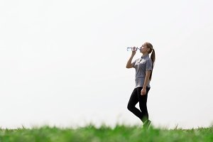 Woman drinking natural water in green field. Concept of health, thirst, hot weather.