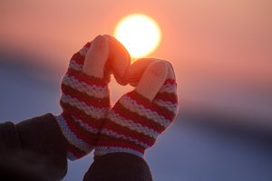Woman hands in winter gloves Heart symbol shaped Lifestyle and Feelings concept with sunset light nature on background