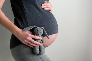 pregnant girl holding a toy rabbit