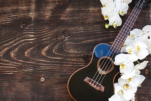 Ukulele and orchid on wooden desk