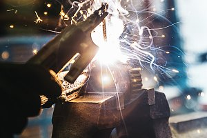 Mechanic man welding metal.