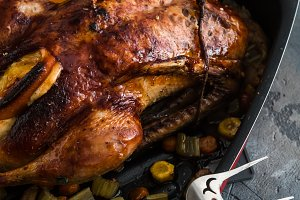 Roast duck and oranges on a black slate board, close view