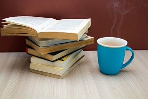 stack of books and hot drink