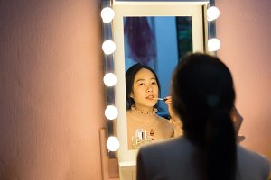 Cute Asian woman doing make-up in front of fashionable mirror with light bulbs