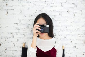 Asian woman pointing a retro camera in front in vintage wall