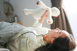 Smiling Asian woman lying down on bed and waking up happily in bedroom -selective focus
