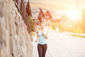 Young athletic girl running on road in the morning