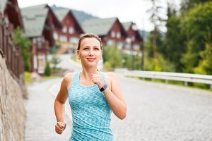 Young fitness woman jogging on street of town