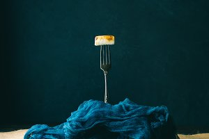 Smoked marshmallow on fork on dark background. Toned