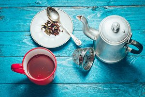 Red tea, teapot and tea leaves