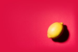 Still life minimalist of a lemon on red background