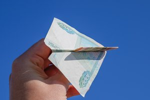Denominations of Russian money, folded in the airplane against the blue sky in hand