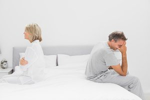 Couple sitting on opposite sides of bed