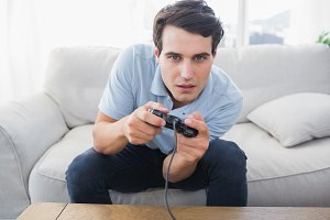 Man having fun with video games while he is sat on a sofa