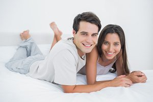 Young couple lying together in bed