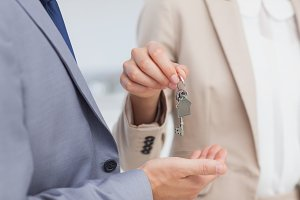 Real estate agent giving house key