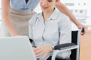 Businesswoman looking at co workers laptop who is sitting in wheelchair